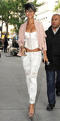 Rihanna In acid washed/Cut up jeans and Bustier+ C. Louboutin Pink snake heels